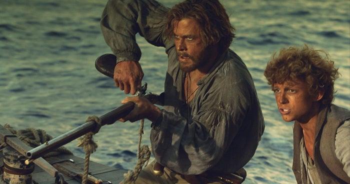"""Chris Hemsworth como Owen Chase e Tom Holland como Thomas Nickerson, no filme de ação/aventura de 2015, """"No coração do Mar""""."""