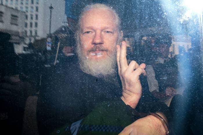 Julian Assange in a police van after his arrest.