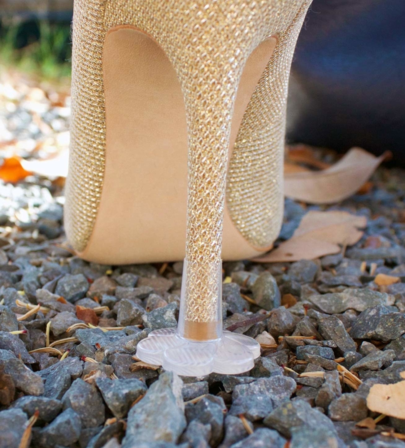 plastic flower-shaped cap on stiletto heel keeping it from sinking into gravel