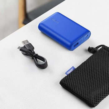 The blue, slightly-larger-than-palm-size power bank with the cord and case
