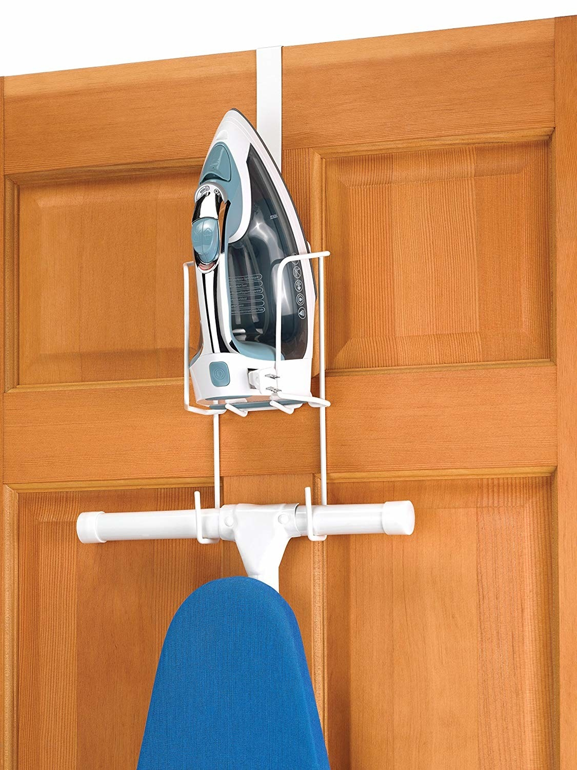 An iron sits in a rack hanging over the door, with hooks beneath it that hold the leg of an ironing board