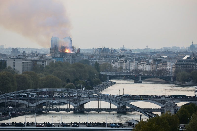 Bystanders stand on bridges across the River Seine as they watch flames and smoke billowing from the roof of Notre-Dame Cathedral in Paris on April 15, 2019. - A fire broke out at the landmark Notre-Dame Cathedral in central Paris, potentially involving renovation works being carried out at the site, the fire service said.Images posted on social media showed flames and huge clouds of smoke billowing above the roof of the gothic cathedral, the most visited historic monument in Europe. (Photo by LUDOVIC MARIN / AFP) (Photo credit should read LUDOVIC MARIN/AFP/Getty Images)