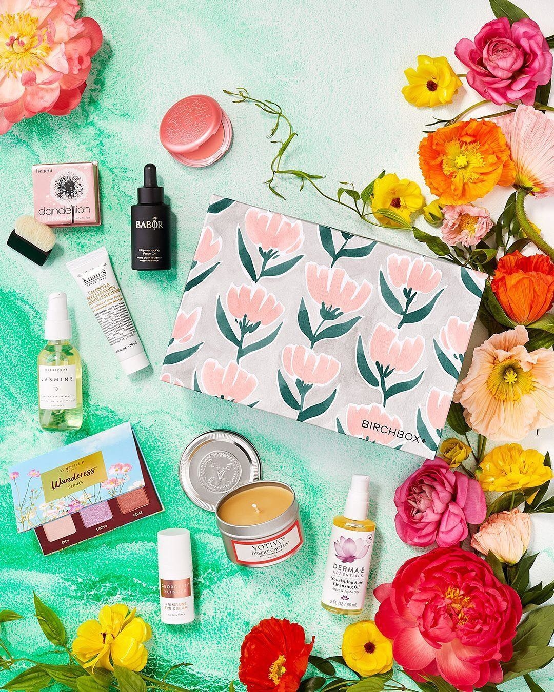 different beauty products styled on table with flowers