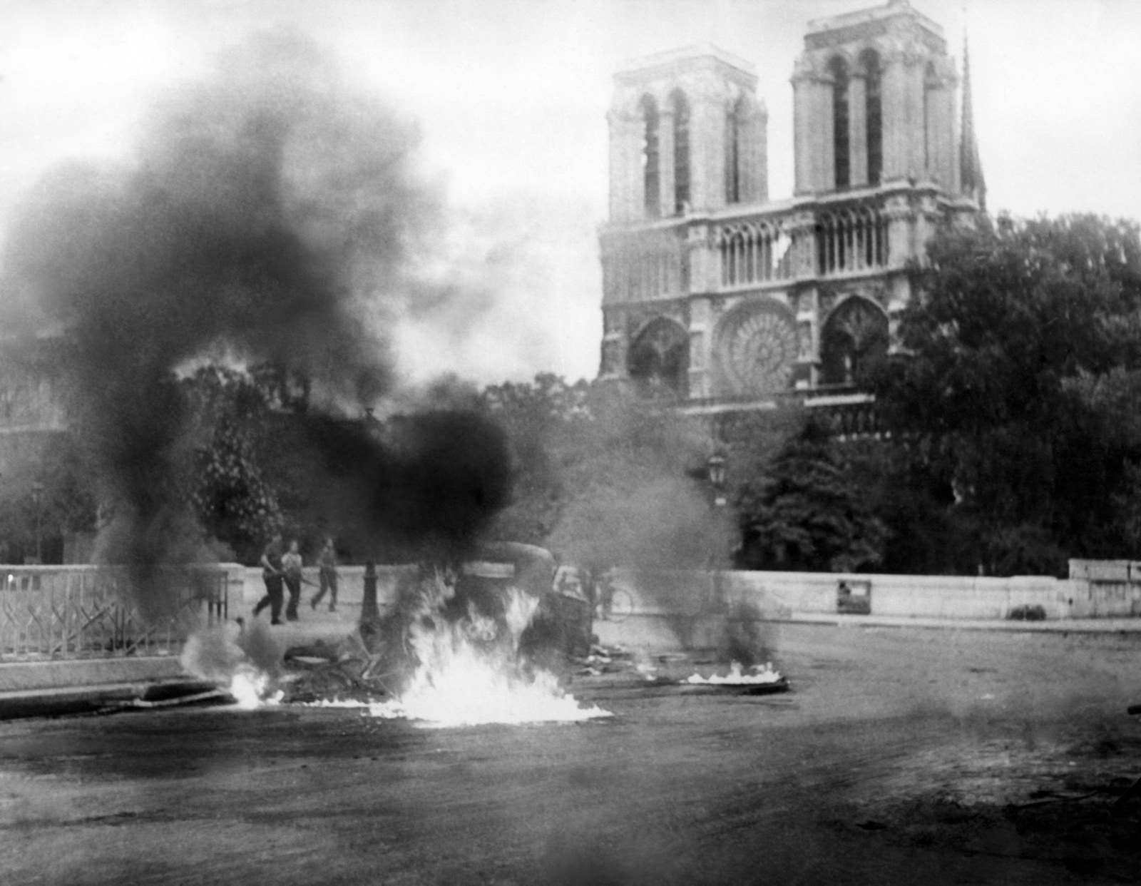 """A photo taken circa Aug. 23, 1944 during World War II shows a flaming vehicle close to the Pont Saint-Michel and Notre Dame Cathedral Notre-Dame as part of the """"Battle of Paris"""" opposing the French Forces of the Interior and remaining Nazi forces, a few days before the Liberation of Paris on Aug. 25, 1944."""
