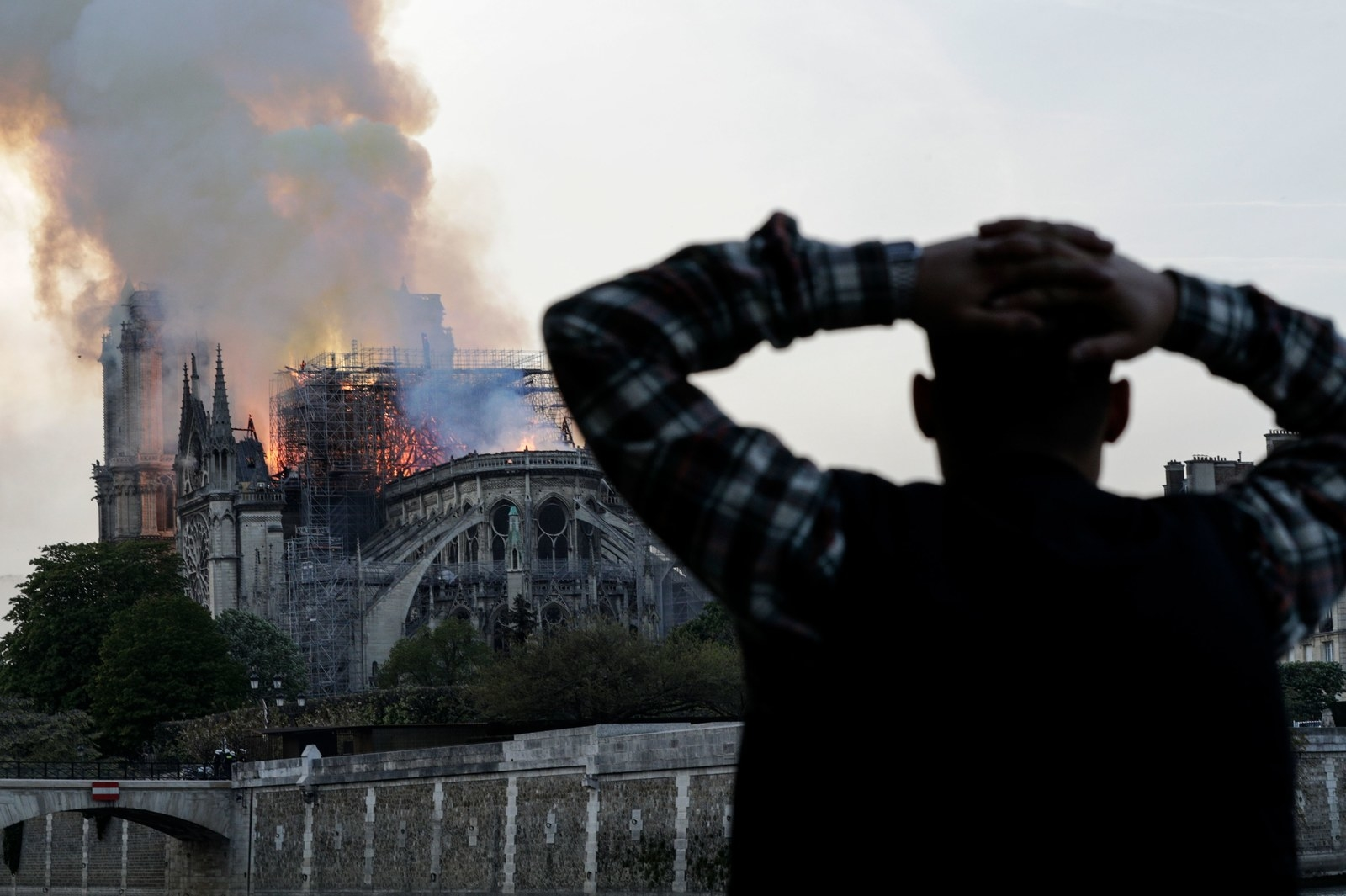 A man watches the landmark Notre-Dame Cathedral, engulfed in flames, in central Paris on April 15, 2019.