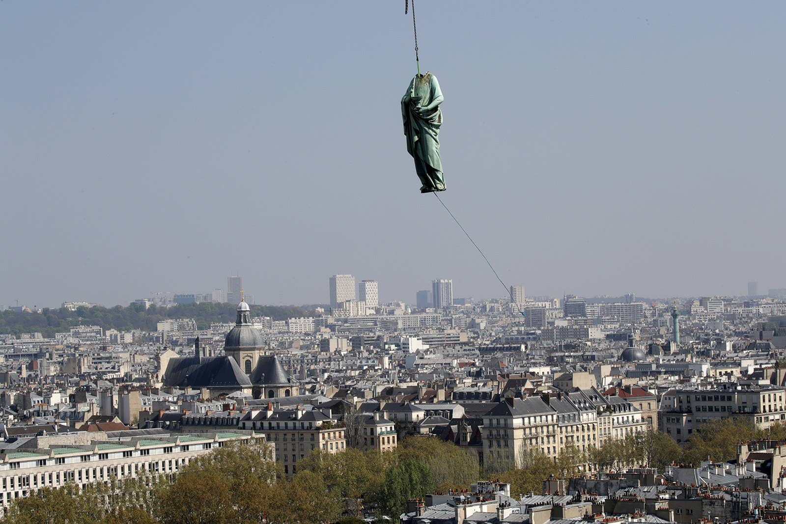 A statue of Saint John is removed from the spire of Notre Dame Cathedral by a crane before restoration work on April 11, 2019.