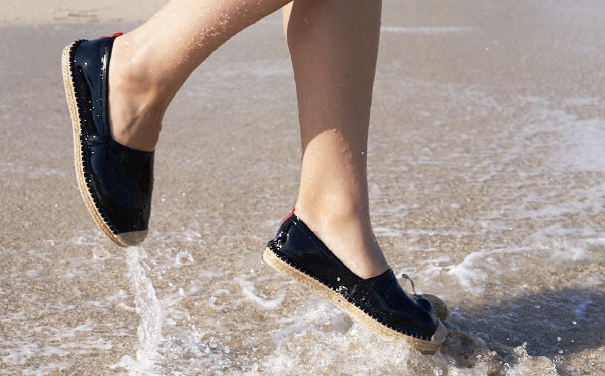 Model wearing the espadrilles while jumping in the water at the beach