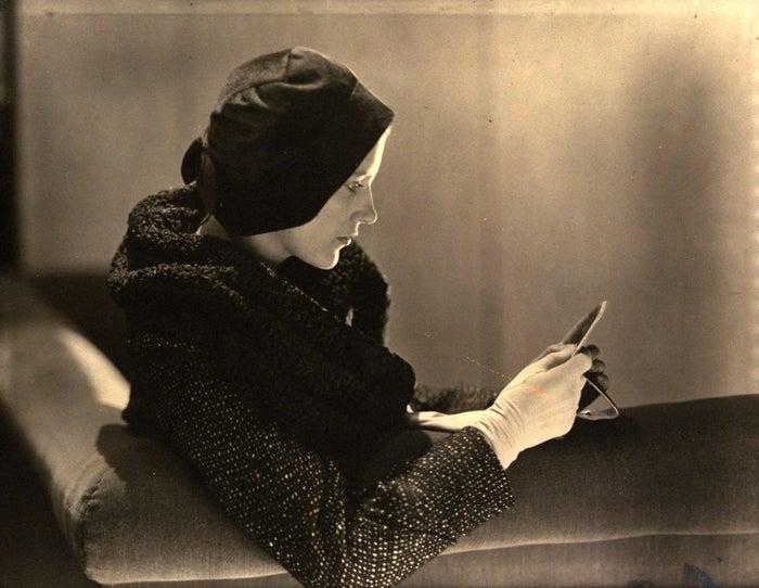 Lee Miller modeling a bonnet-style hat by designer Rose Descat with a Weil coat, 1930.