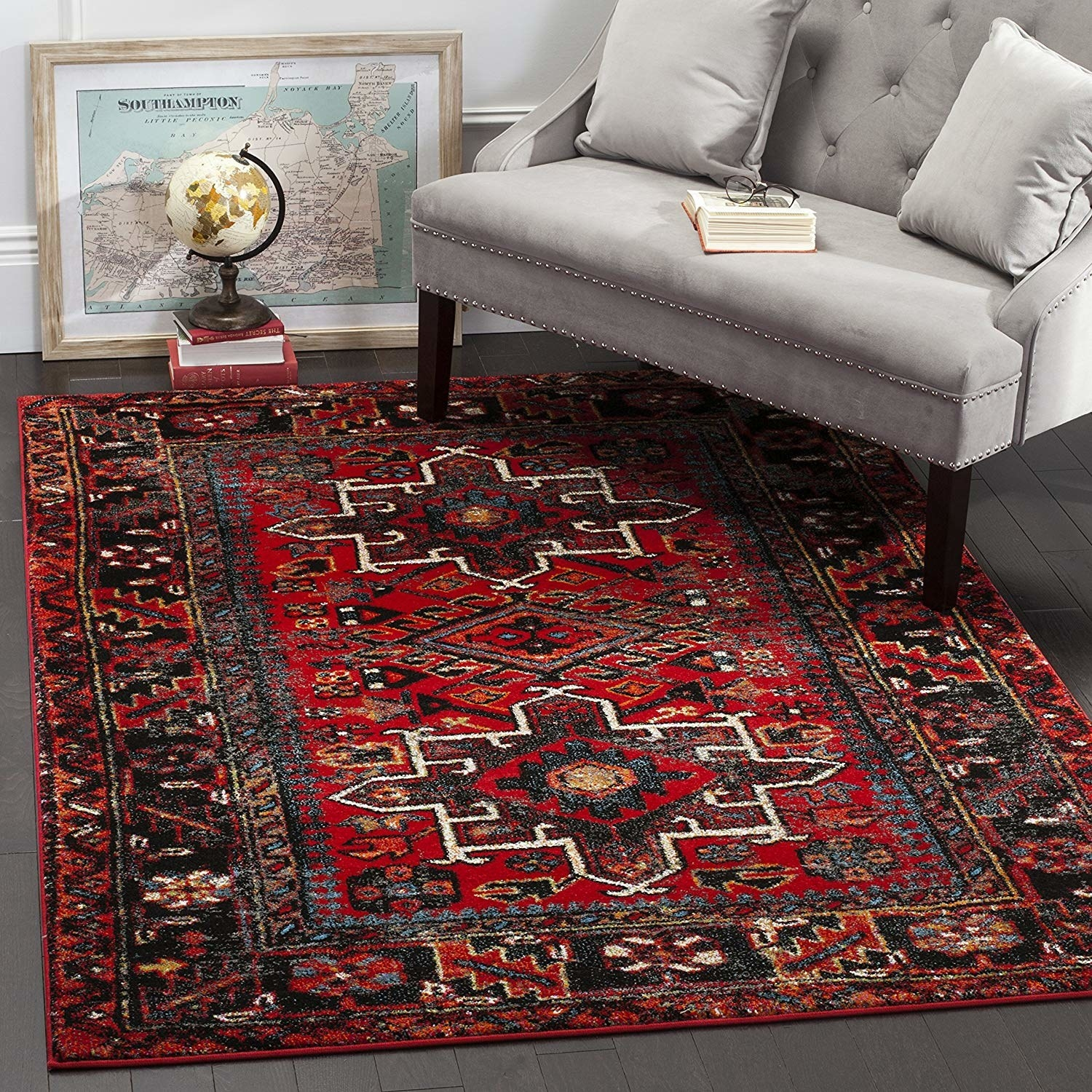 A traditional Turkish patterned red rug placed in a room with gray walls and furniture