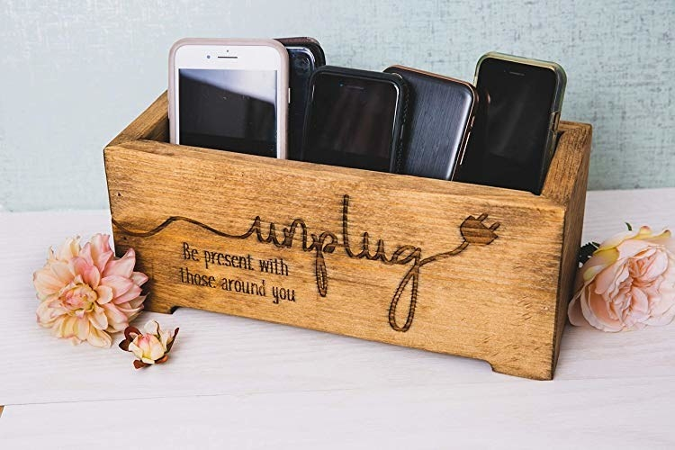 "rectangle wood holder with phones inside and the words ""Unplug, be present with those around you"" on the front"