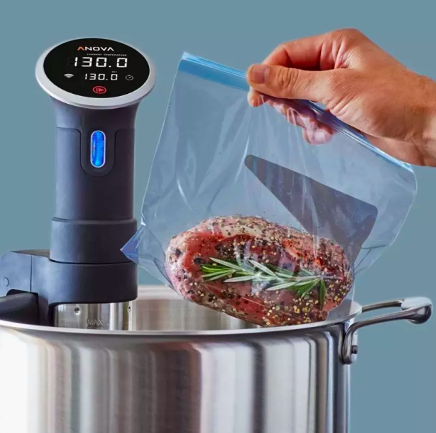 Hand placing a zip-top bag with meat in a pot with the sous vide