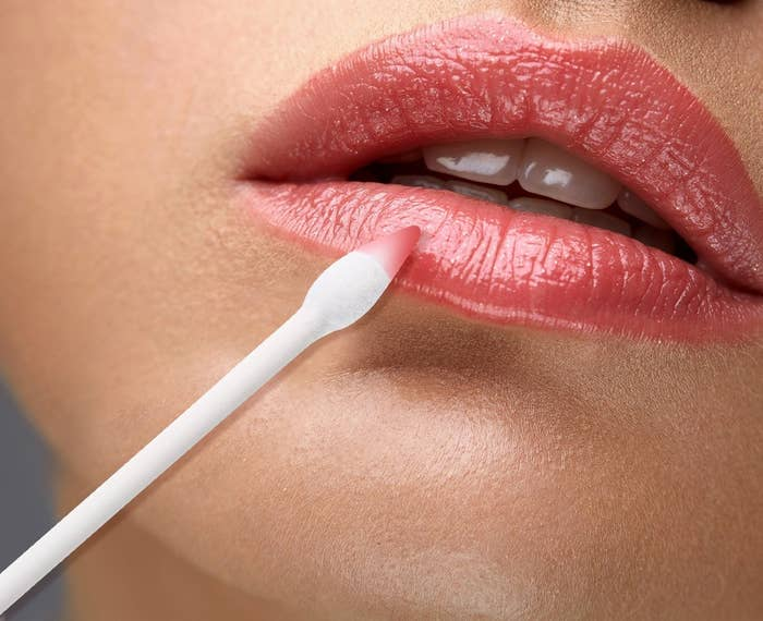 Model using pointed cotton swab on lips