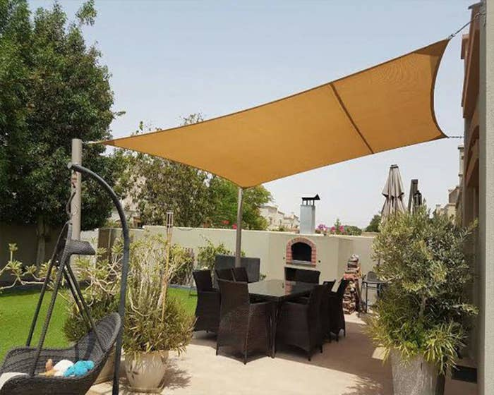 The canopy stretching over a patio dining set in a yard