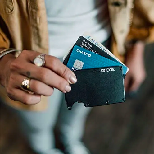 A model holding the slim wallet. It is filled with three cards.