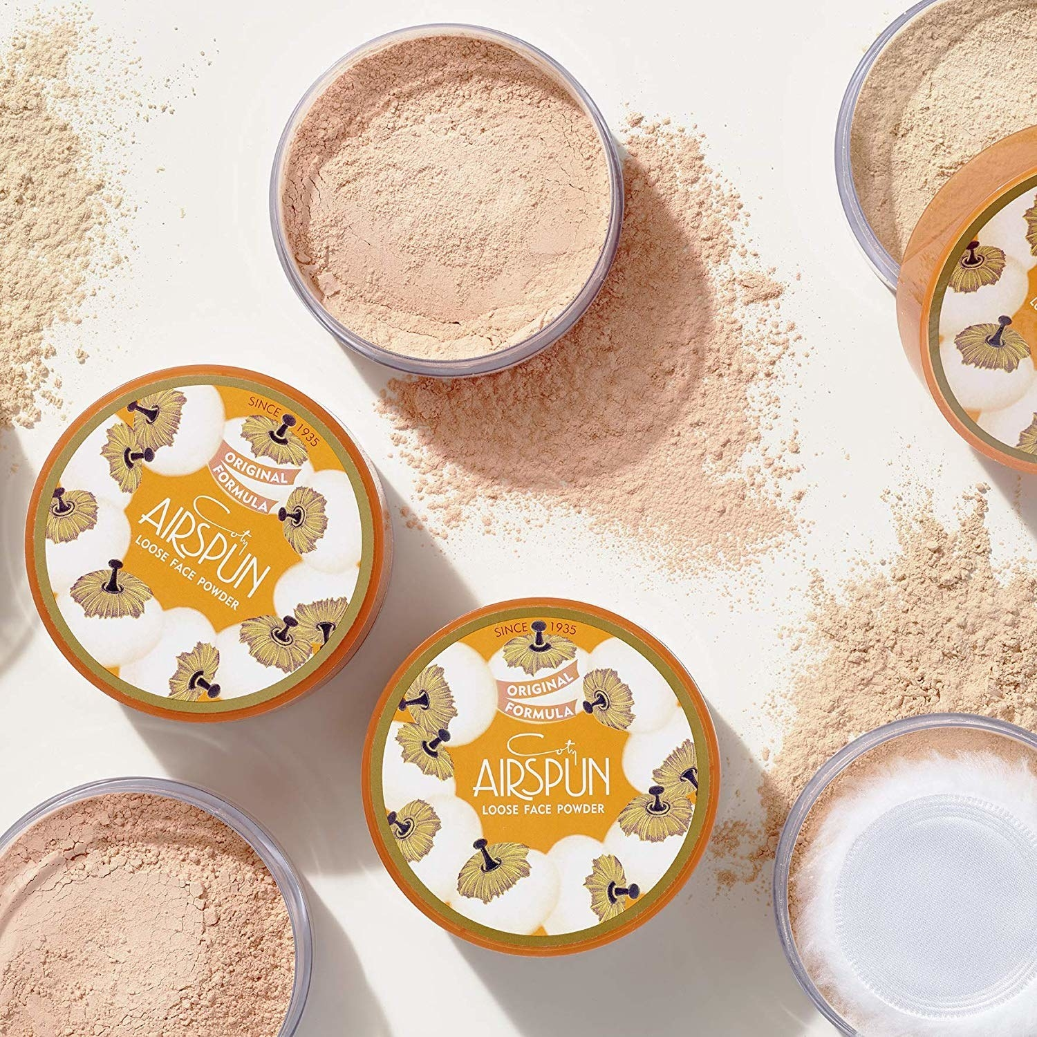 Some scattered containers of the Coty Airspun loose setting powder.