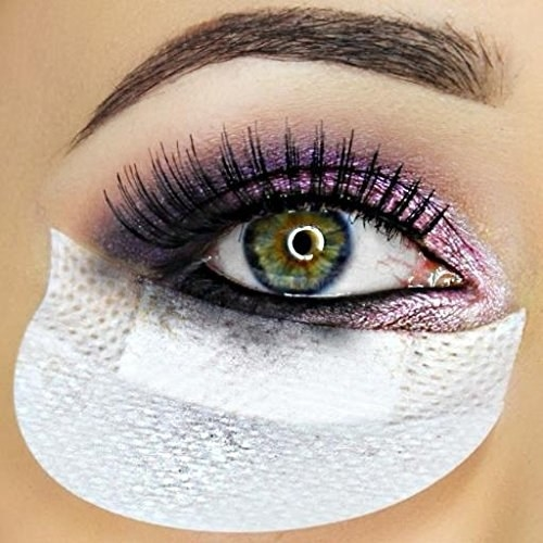 A closeup of an eye with the Shadow Shield placed under it to catch excess makeup.