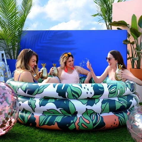 a group of three adults drinking out of pineapple cups and splashing into a mini blow up pool with a leafy design all over it