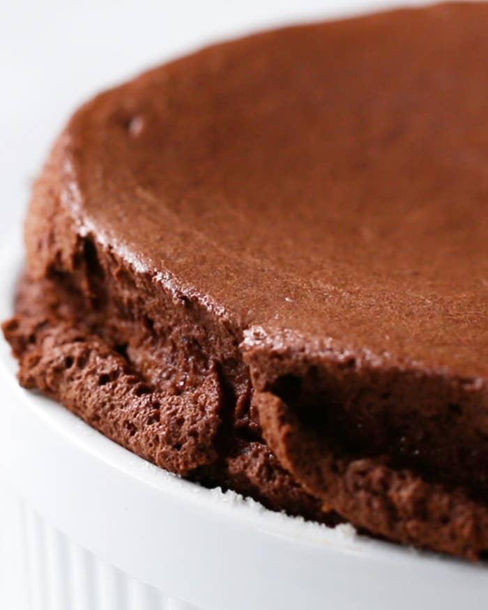 10人分材料:無塩バター(室温に戻しておく) 大さじ2グラニュー糖 150g牛乳 600mlチョコレート(刻む) 340g卵(卵黄と卵白に分ける) 6個薄力粉 30g塩 小さじ1/2バニラエクストラクト 小さじ1乾燥卵白 小さじ1/2粉糖 適量ホイップクリーム お好みで作り方:1.オーブンは200℃に予熱しておく。2.ココット皿の内側に柔らかくなったバターを塗り、50gの砂糖を全体にまぶす。3.鍋に牛乳を入れて中火にかけ、沸騰直前に火からおろし、刻んだチョコレートを加えてなめらかになるまで混ぜる。4.ボウルに卵黄、砂糖50g、小麦粉、塩、バニラエクストラクトを加えてなめらかになるまで混ぜる。5.(3)の半量を(4)に加え、なめらかになるまで混ぜる。6.(3)の残りは再び中火にかける。温まったら(5)を加えて、もったりとするまで絶えずかき混ぜる。7.ボウルに移し、表面が乾かないようにぴったりとラップで覆い、粗熱が取れたら冷蔵庫で30分冷やす。8.メレンゲを作る。ボウルに卵白、乾燥卵白を加え、ハンドミキサーで泡立てる。全体が白っぽくなったら砂糖50gを2回に分けて加え、ツノが立つまで泡立てる。9.(7)にメレンゲを3回に分けて加え、ゴムベラで気泡をつぶさないようにさっくりと混ぜる。10.ココット皿に生地を流し入れ、親指の腹で生地の淵をココットの内側に添わせる。11.オーブンの温度を190℃に下げて、(10)を入れて十分膨らむまで45-50分焼く。12.粉糖をふるってホイップクリームをトッピングしたら、完成!