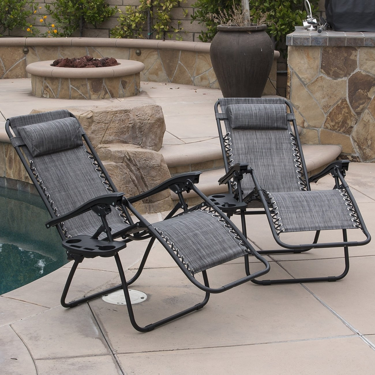 Two grey lounge chairs by a pool