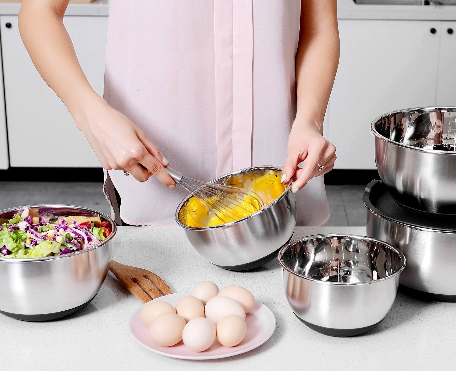 Model whisking eggs in a bowl, with ingredients in the other ones
