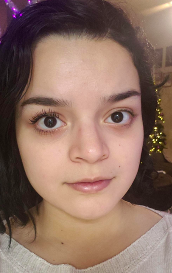 A reviewer with the mascara on one eye showing the length it creates when applied