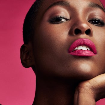 Model wearing the lip paint in a bold pink