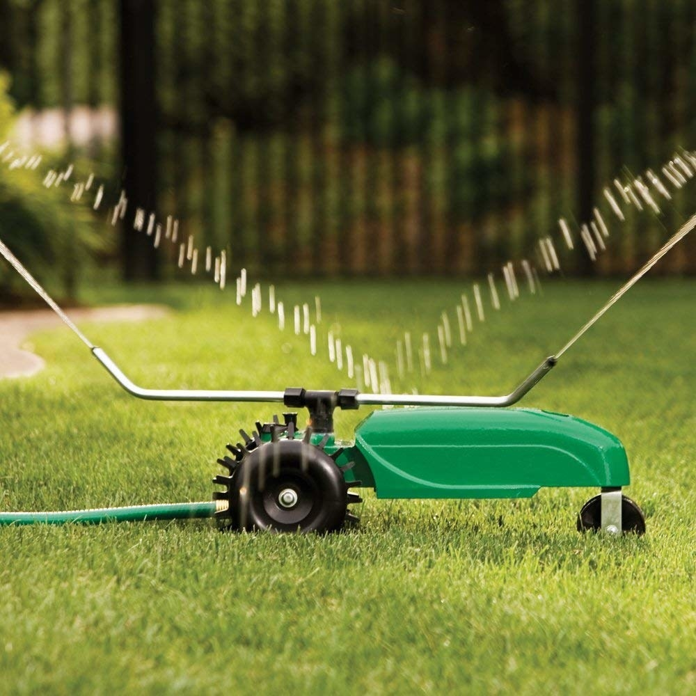 Green sprinkler with water sprinkling over grass