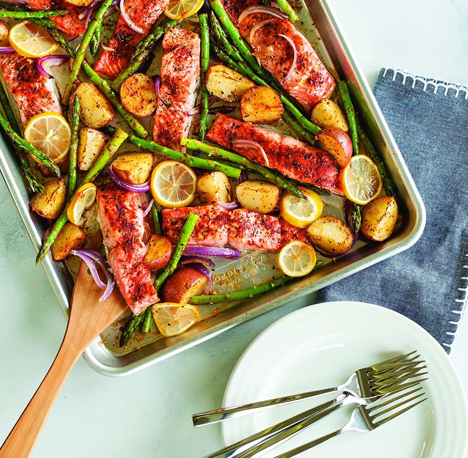 A sheet pan with salmon, potatoes, lemon slices, and asparagus on it