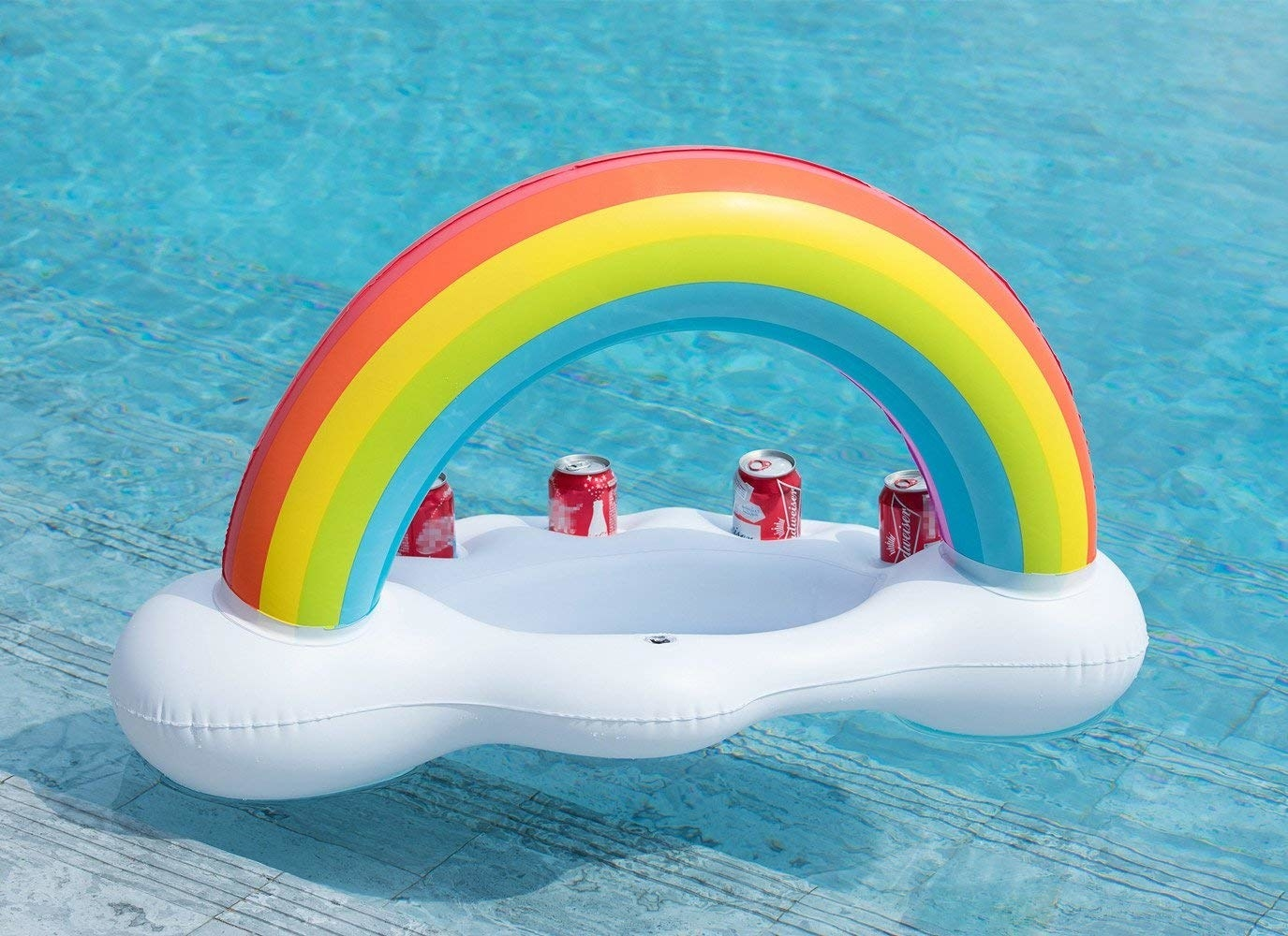 Floating beverage bar in the shape of a rainbow with clouds beneath it where four soda cans sit