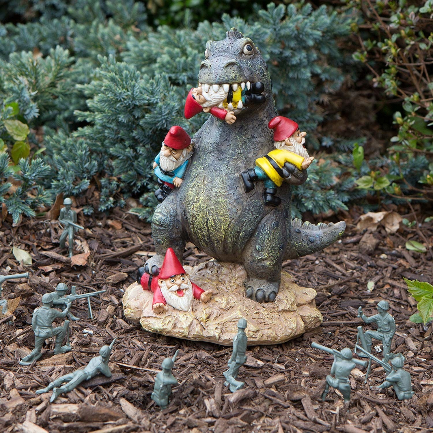Godzilla lawn ornament attacking gnomes with toy army characters surrounding it in a garden