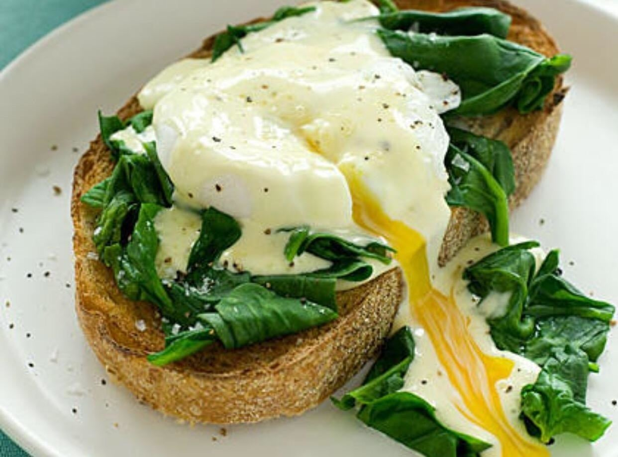 A perfectly poached egg on bread with some greens