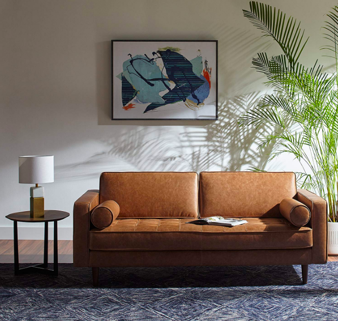 A lifestyle shot of the mid-century style sofa with wooden legs, two long round pillows beside the arm rests, two upright back cushions, and a tufted seat cushion