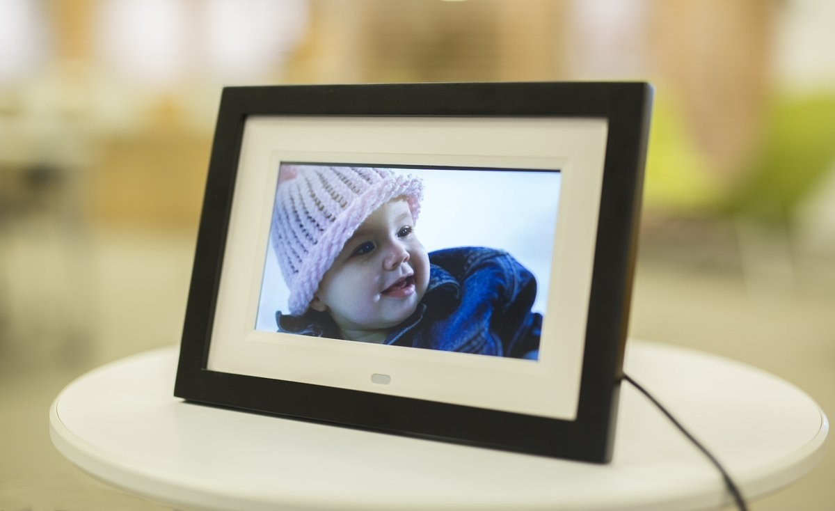 The frame plugged into the wall displaying a photo of a baby on its screen