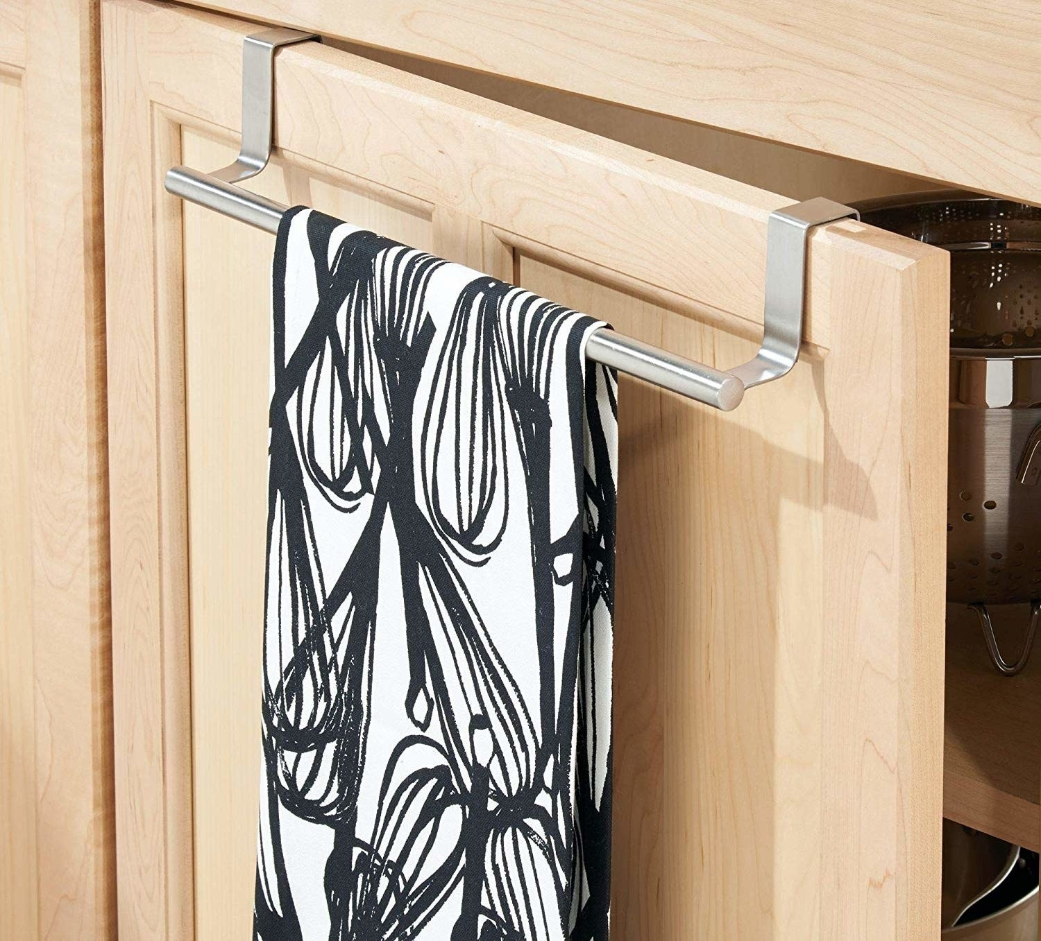 A metal bar hanging over a kitchen cabinet, holding a folded dish towel