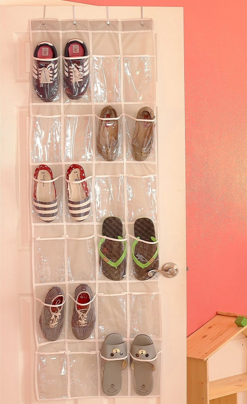 A clear over-the-door organizer with some of the pockets holding one shoe each