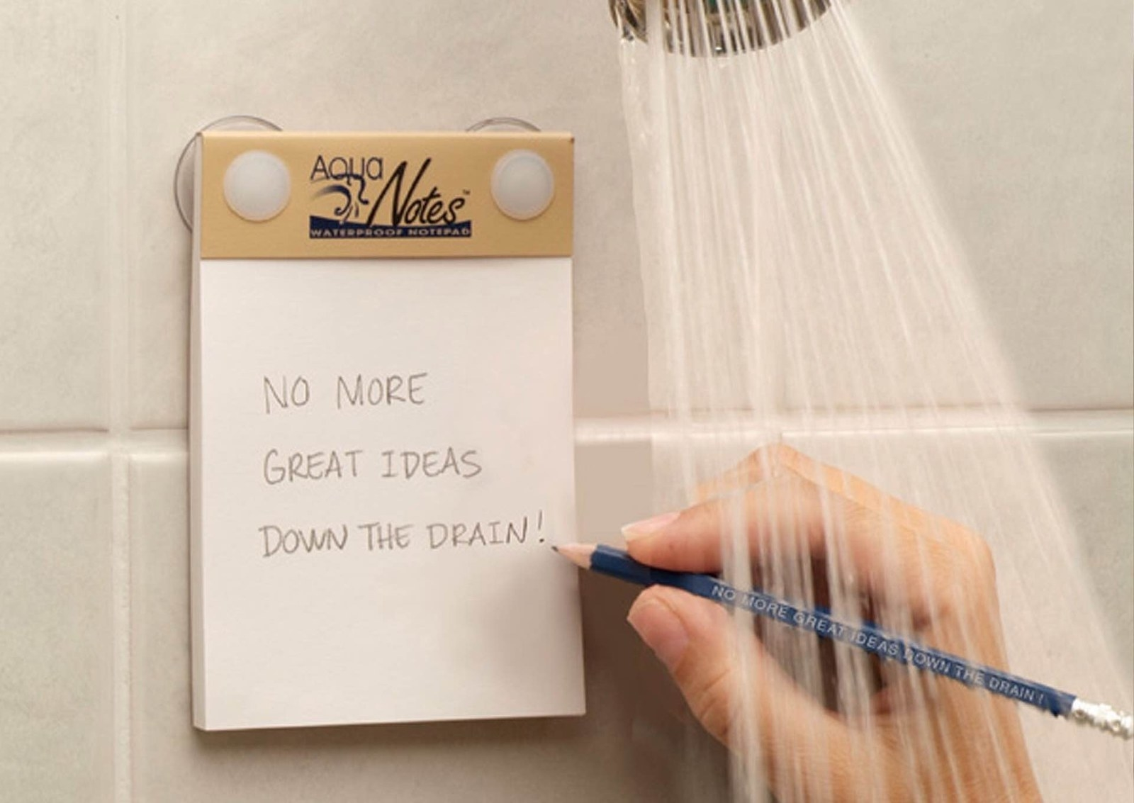 "A water-proof note pad suctioned onto a shower wall as a person writes ""no more great ideas down the drain!"" on it"