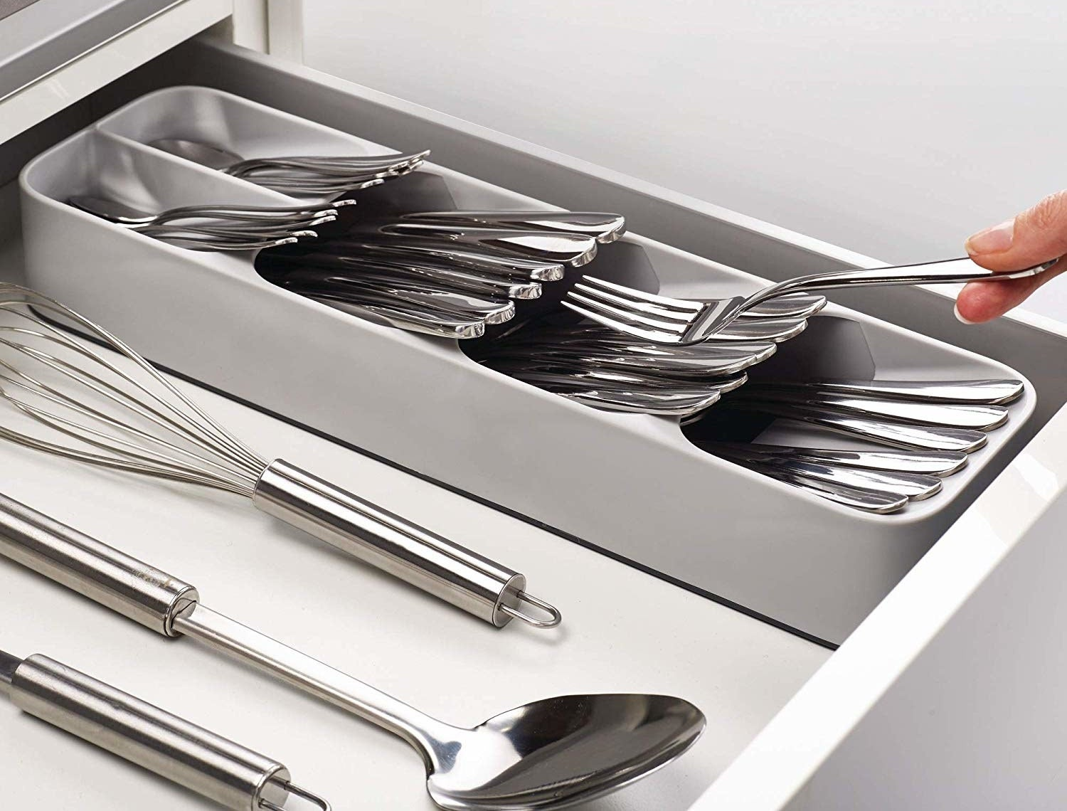 A cutlery organizer inside of a drawer with three big compartments and two smaller compartments at the top filled with silverware