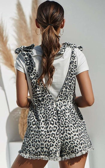 A model showing the shortalls from the back, which has a plunging V down to the waist