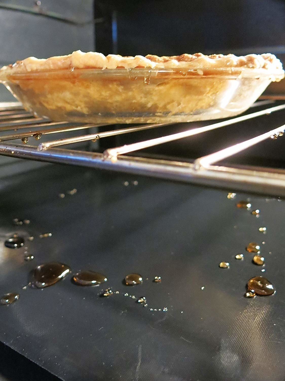 oven liner catching drips from pie inside oven