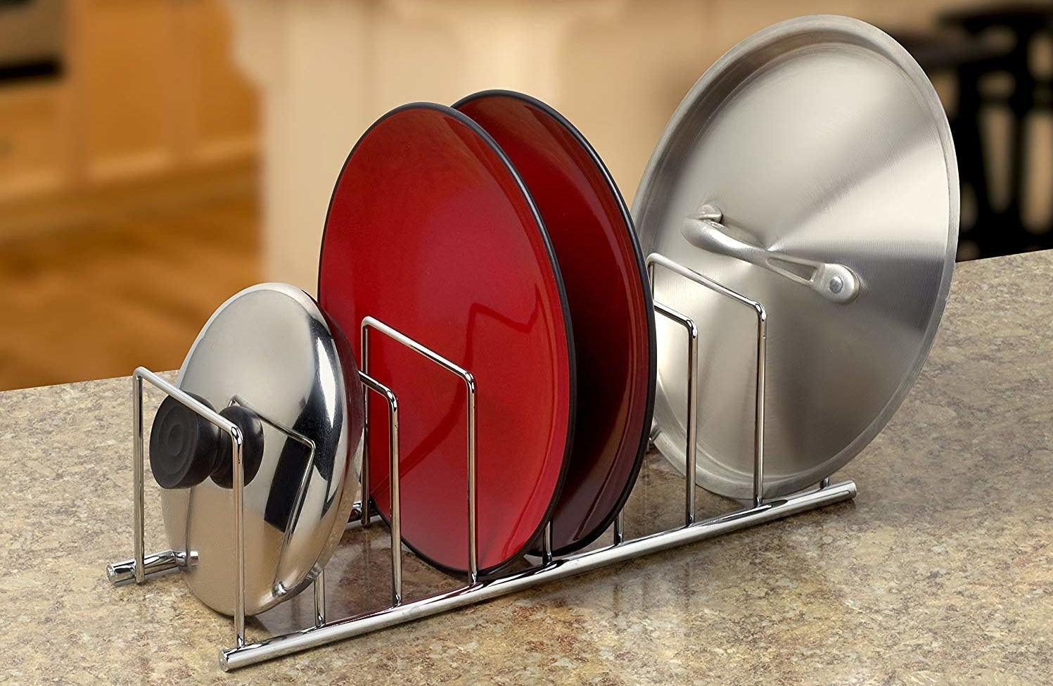 A metal rack holding a pot lid, two plates, and a pan lid of varying sizes, with four more free compartments for holding kitchenware