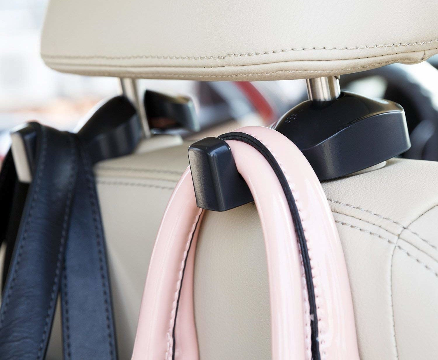 Hooks attached to the car headrest each holding what appear to be handbag straps