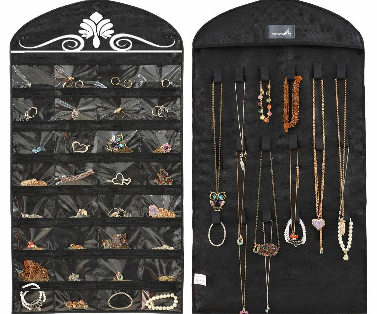 A two-sided jewelry organizer that has 32 clear pockets on the left side filled with things like rings and bracelets, and 18 hook and loop closures on the right side holding necklaces
