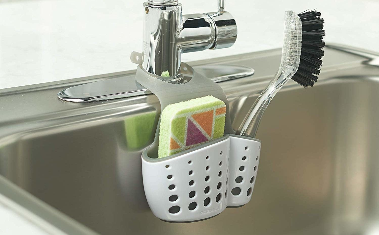 A white caddy hanging onto a sink, holding a sponge and a dish-scrubbing brush