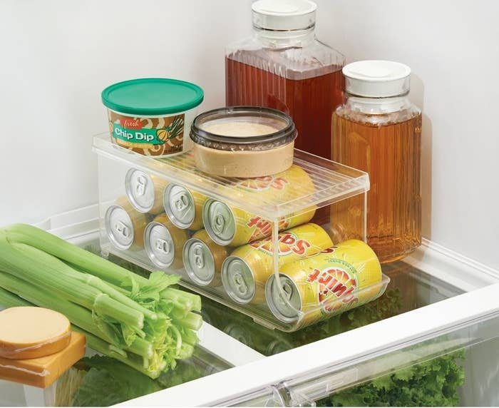 shelf of fridge with a few drink pitchers and a deep soda can organizer with cans organized horizontally for easy removal each time
