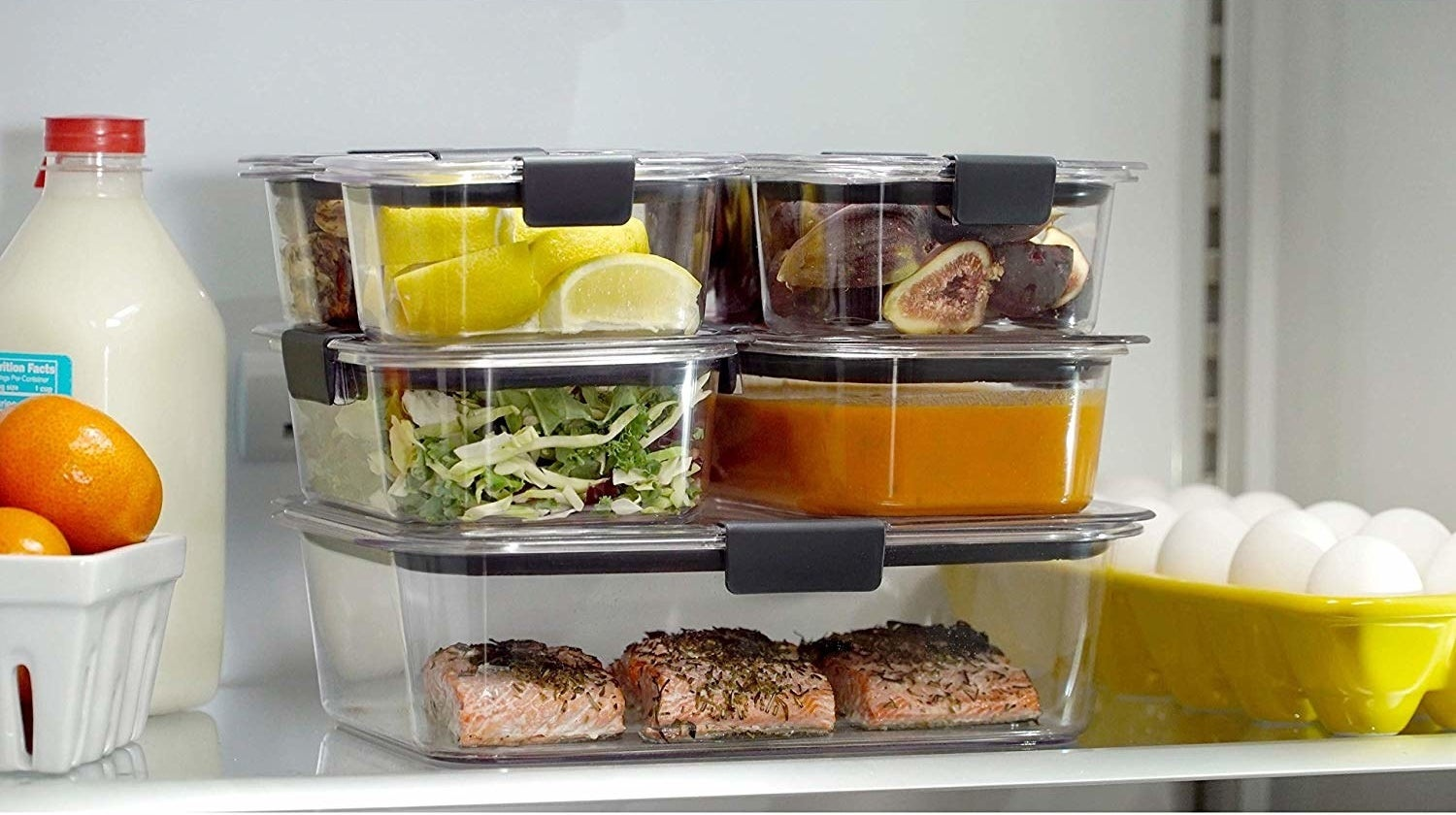 stack of clear food storage containers in a fridge