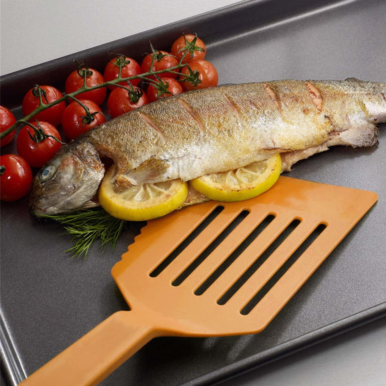 The orange spatula sliding under a fish on a pan