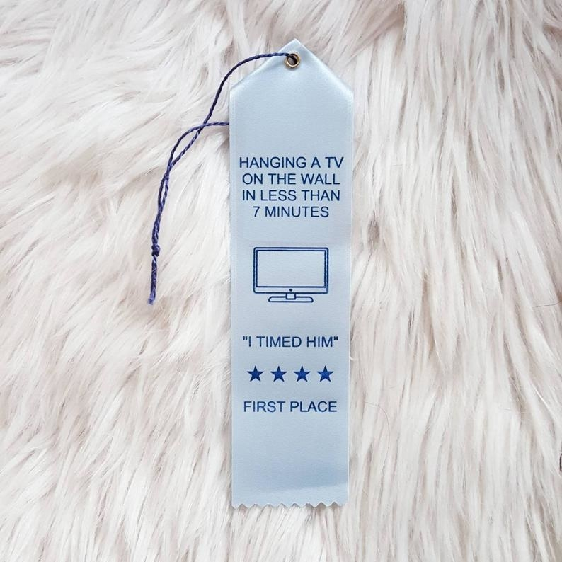 """a blue award ribbon that says """"hanging a tv on the wall in less than 7 minutes"""" on it"""
