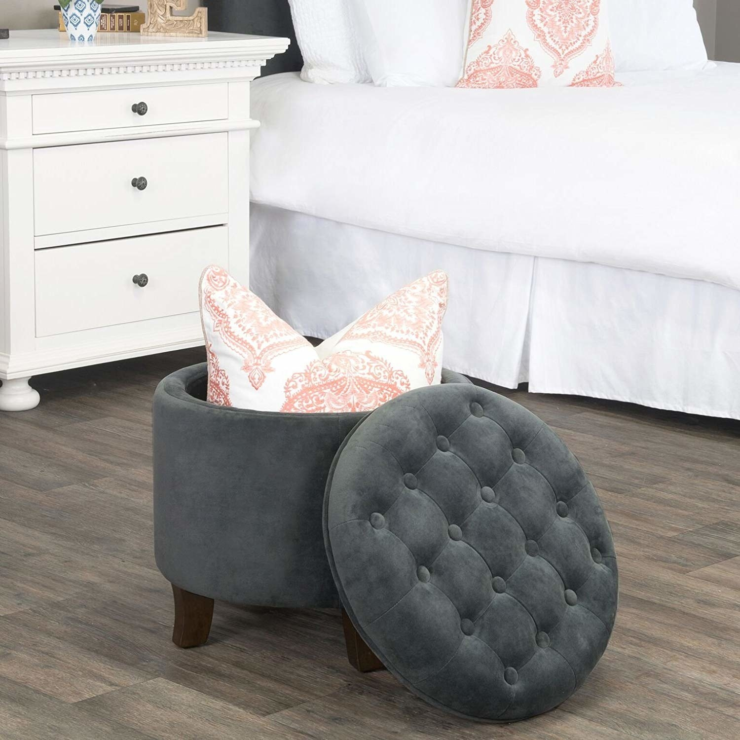 round upholstered dark gray storage ottoman with a pillow stored inside