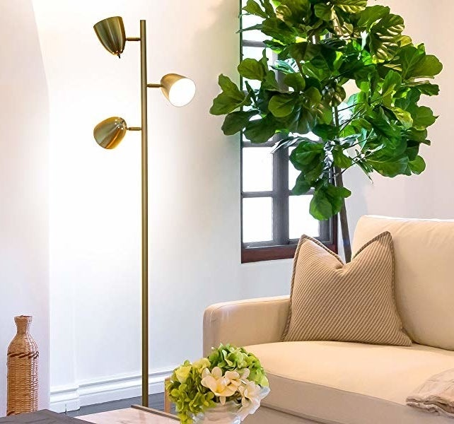 living room corner with gold tone floor lamp with three arms on it