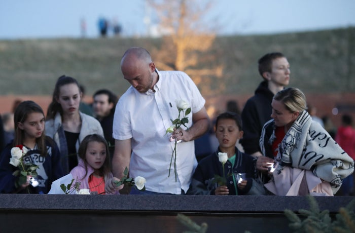 Will Beck, a survivor of the 1999 shooting, and his family place roses at the memorial the victims of the massacre during a vigil Friday.